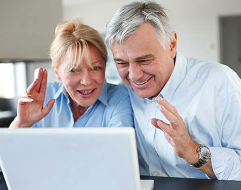 Couple waving hands at computer